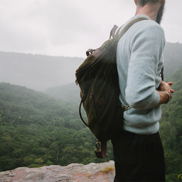 man-with-backpack-standing-on-cliff-of-forest-africa-fursa
